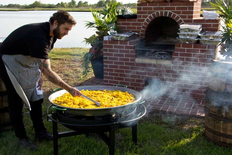 man stirring giant pan of paella