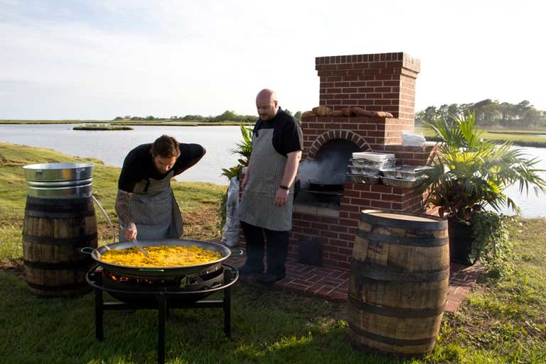 two men outside with giant pan of paella